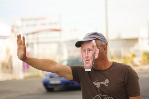 Un militant, masque de Gérard Mulliez sur le visage, remercie les clients de Décathlon de venir « remplir son porte monnaie ». (CP/Rue89 Bordeaux)