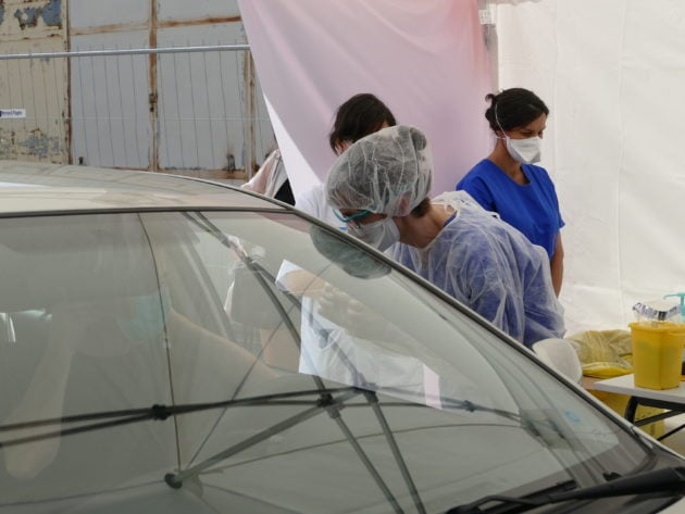 Une infirmière de l'Hôpital Pellegrin procède au test d'un automobiliste potentiellement malade, en réalisant un prélèvement naso-pharyngé à l'aide d'un écouvillon. L'échantillon partira ensuite dans un laboratoire du CHU de Bordeaux. ©Florence Heimburger